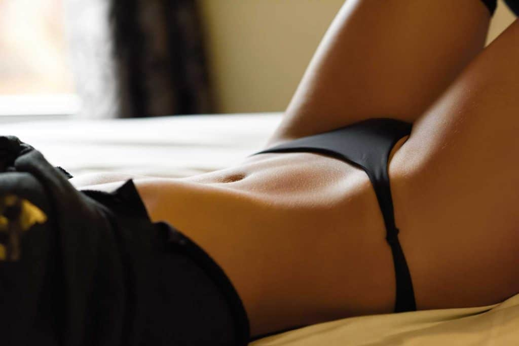 Chase Strippers - Woman Laying on Bed in Black Lingerie